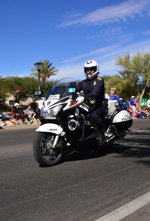 Police officer riding motorcycle during parade