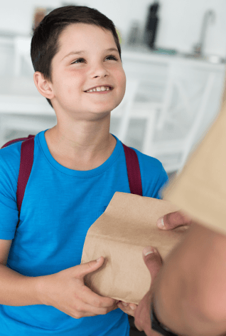 Photo of young boy accepting a sack full of food