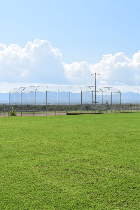 Green grass with ball field, mountains and white puffy clouds in the distance.